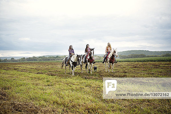 Female friends riding on horses against sky