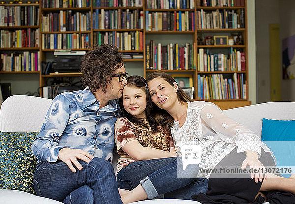 Mädchen mit Eltern  die zu Hause auf dem Sofa sitzen
