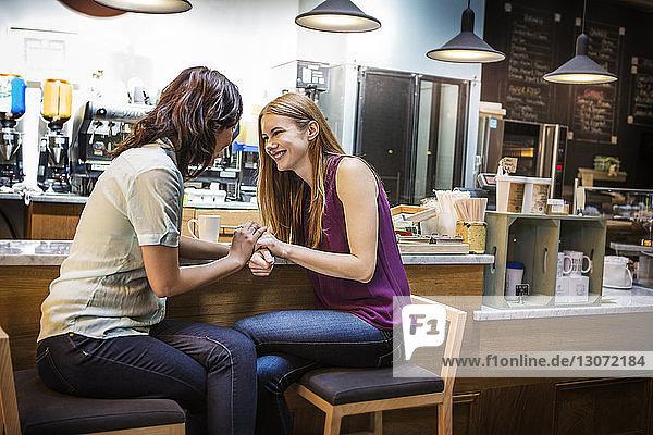 Fröhliche Freunde unterhalten sich am Tresen eines Cafés