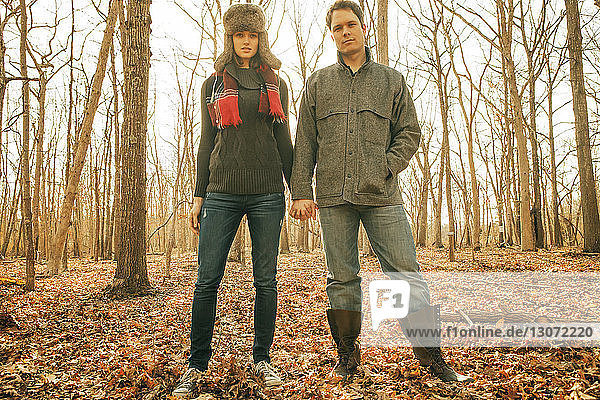 Portrait of couple holding hands while standing in forest