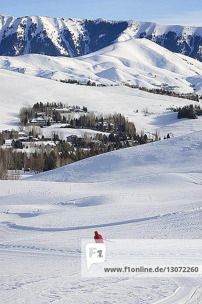 Fernsicht einer Frau beim Skifahren auf schneebedecktem Feld