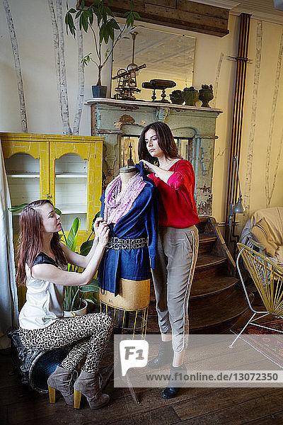 Besitzer arrangieren Kleidung auf Schaufensterpuppe während der Arbeit im Laden