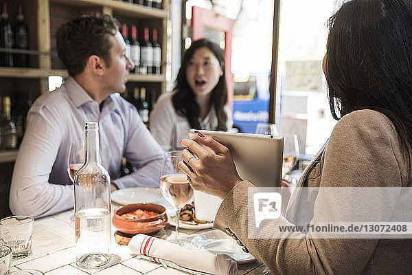 Frau zeigt Tablet-Computer  während sie im Restaurant am Tisch sitzt