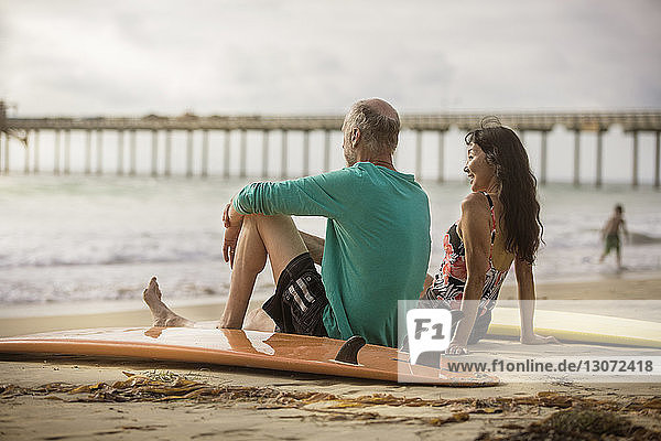 Rear view of senior couple sitting on shore at beach