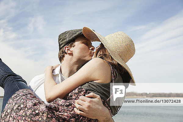 Man kissing girlfriend while carrying at beach