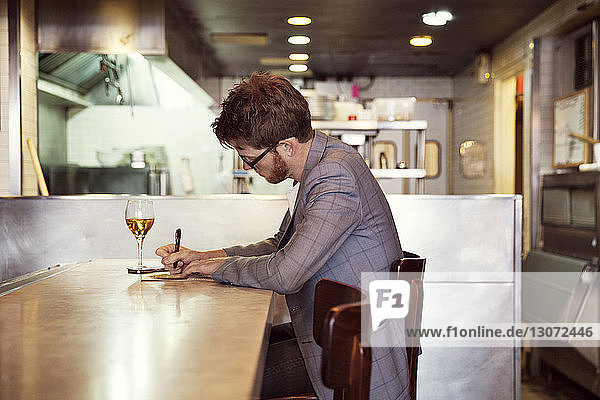 Side view of man writing while sitting at table in restaurant