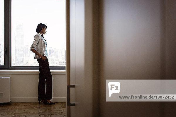 Woman looking away seen through office doorway