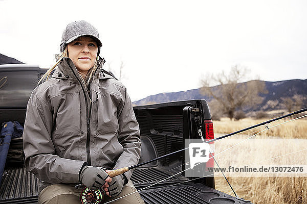 Portrait of woman holding fishing rod while sitting on pick-up truck