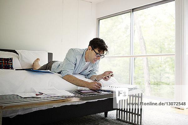 Mann hört Musik  während er zu Hause im Schlafzimmer an einem Dokument arbeitet