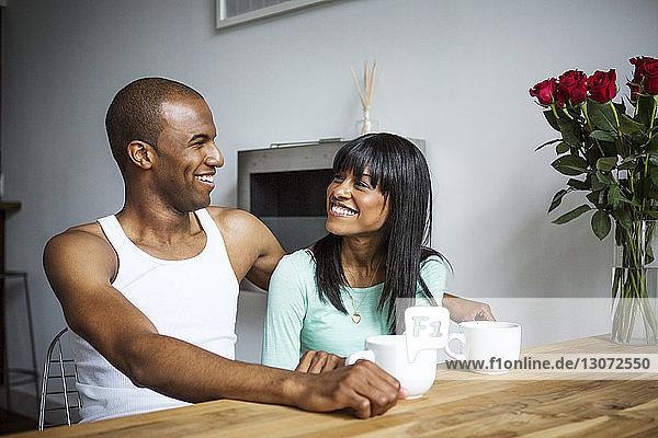 Glückliches Paar unterhält sich zu Hause am Tisch
