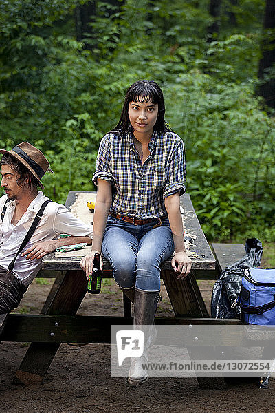 Portrait of woman holding beer bottle while sitting with friend on picnic table in forest