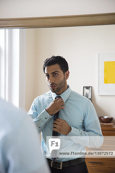 Man adjusting necktie while standing in front of mirror at home
