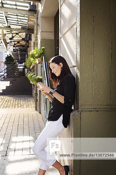 Seitenansicht einer Frau  die ein Mobiltelefon benutzt  während sie sich auf der Straße an die Wand lehnt