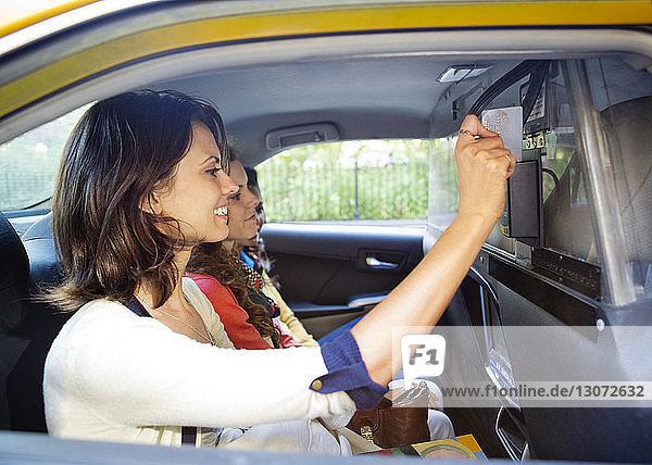 Frau bezahlt fair mit Kreditkarte  während sie mit Freunden im Taxi unterwegs ist