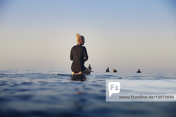 Rear view of woman resting on surfboard on sea against clear sky