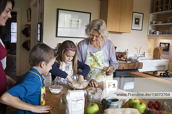 Family looking at girl mixing flour in bowl at home