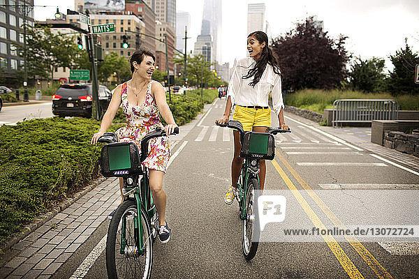 Fröhliche Freunde fahren Fahrrad auf der Straße
