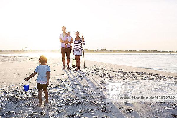 Familie in voller Länge am Strand gegen den Himmel an einem sonnigen Tag