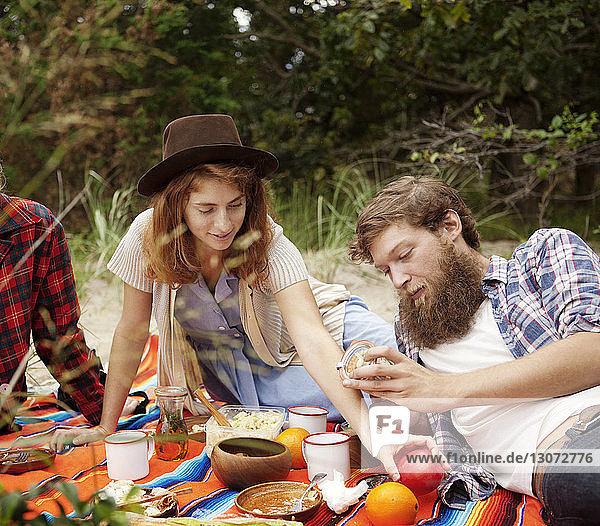 Freunde beim Frühstück  während sie sich auf einem Feld im Wald entspannen