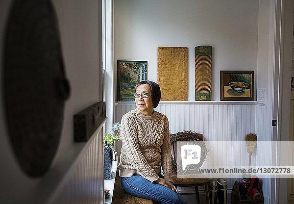 Nachdenkliche Frau schaut weg  während sie zu Hause am Fenster sitzt