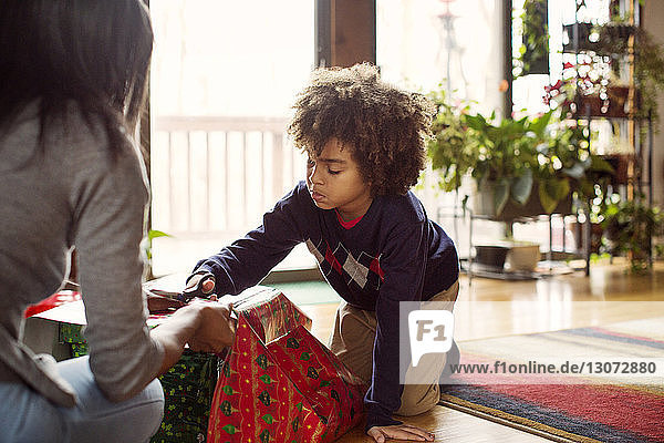 Mother and son wrapping Christmas present at home