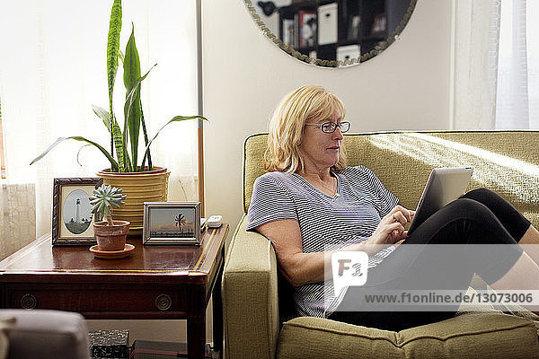 Woman using tablet computer while sitting on sofa at home