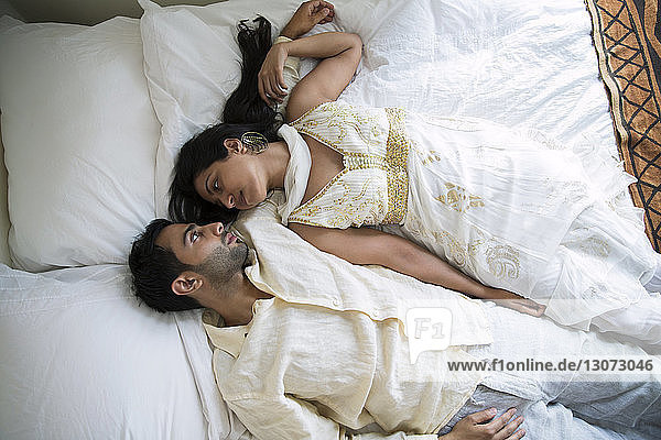 Overhead view of couple lying on bed at home