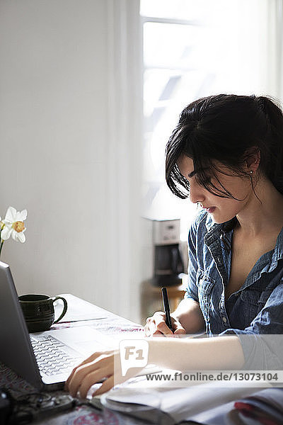 Woman writing recipe from laptop computer while sitting at home