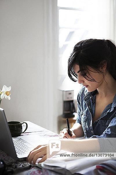 Frau schreibt zu Hause am Laptop ein Rezept