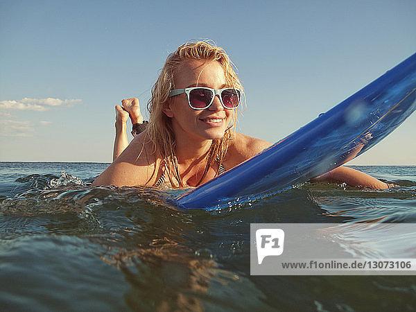 Woman lying on surfboard in sea against sky