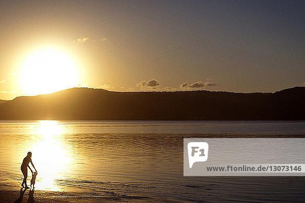 Silhouette einer Mutter mit Sohn bei Sonnenuntergang am Strand