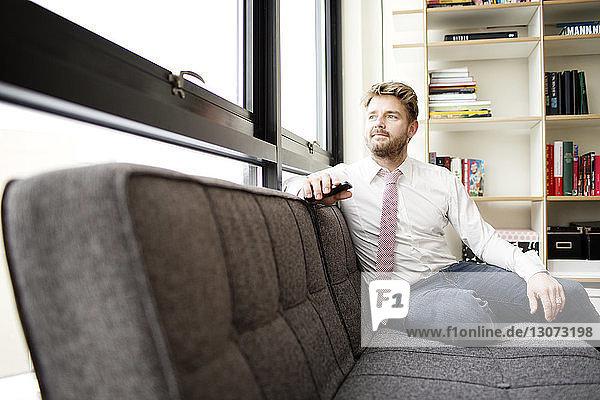Mann schaut weg  während er zu Hause auf dem Sofa sitzt