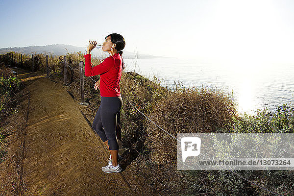 Woman drinking water while standing on road against sea