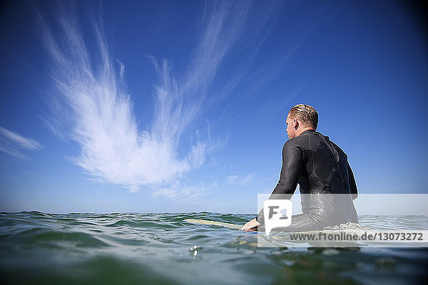 Rear view of man sitting on surfboard in sea against sky
