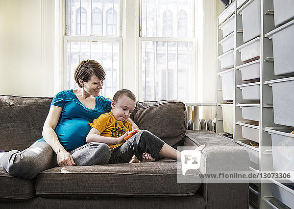 Pregnant woman with son sitting on sofa at home