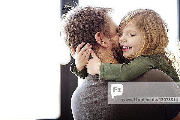 Glücklicher Vater umarmt Tochter zu Hause