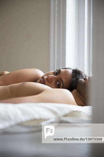 Porträt einer Frau mit einem zu Hause auf dem Bett liegenden Mann