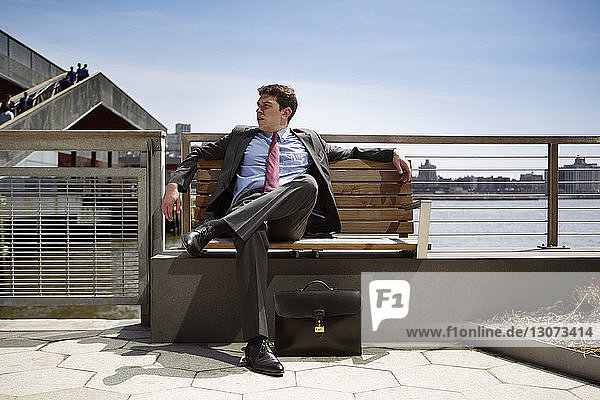 Businessman looking away while sitting on bench against sea