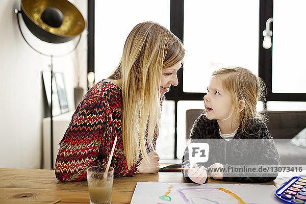 Mädchen sieht Mutter an  während sie zu Hause einen Pinsel hält
