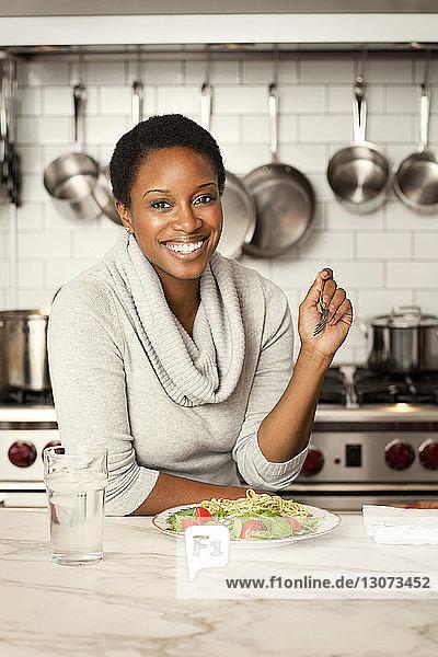 Porträt einer Frau  die auf einer Kücheninsel Nudeln isst
