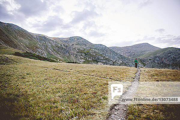 Distanzansicht einer Frau  die auf einem Pfad in den Bergen gegen den Himmel steht