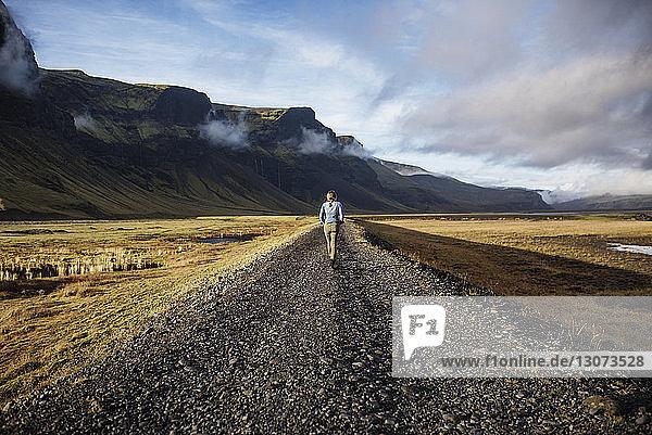 Rückansicht einer Frau  die auf einem Feldweg durch Berge gegen den Himmel läuft