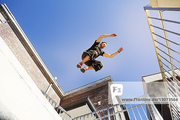 Low angle view of man jumping on buildings against clear blue sky