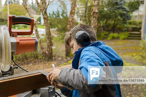 Boy wearing ear protectors while measuring wooden plank at backyard