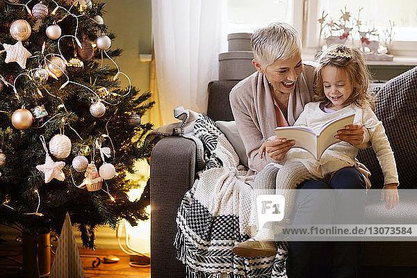 Großmutter und Mädchen lesen Buch  während sie zu Hause auf dem Sofa sitzen