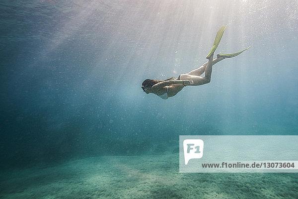 Seitenansicht einer im Meer schwimmenden Frau