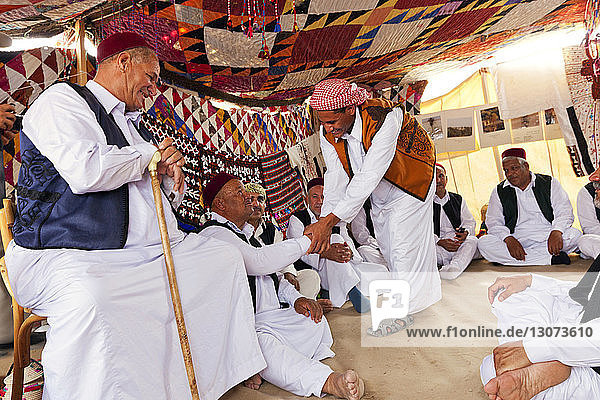 Men talking while sitting in tent at Pushkar Fair