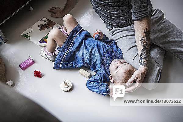High angle view of father sitting by daughter lying on floor at home