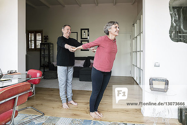 Älterer Mann assistiert Frau beim Yoga