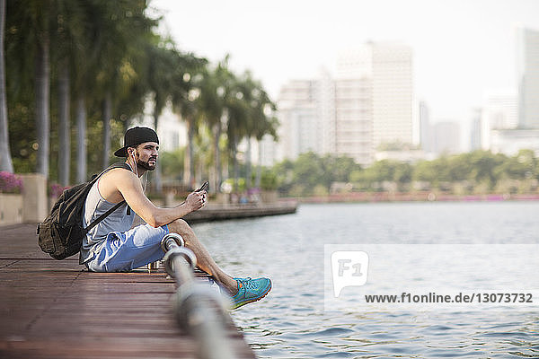 Thoughtful man listening music with headphones and sitting on wooden walkway at riverbank